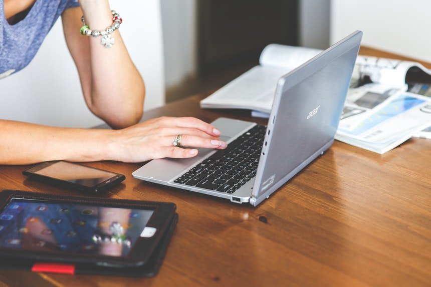 A woman is reading a blog about the resume writing tips she can use to write her own