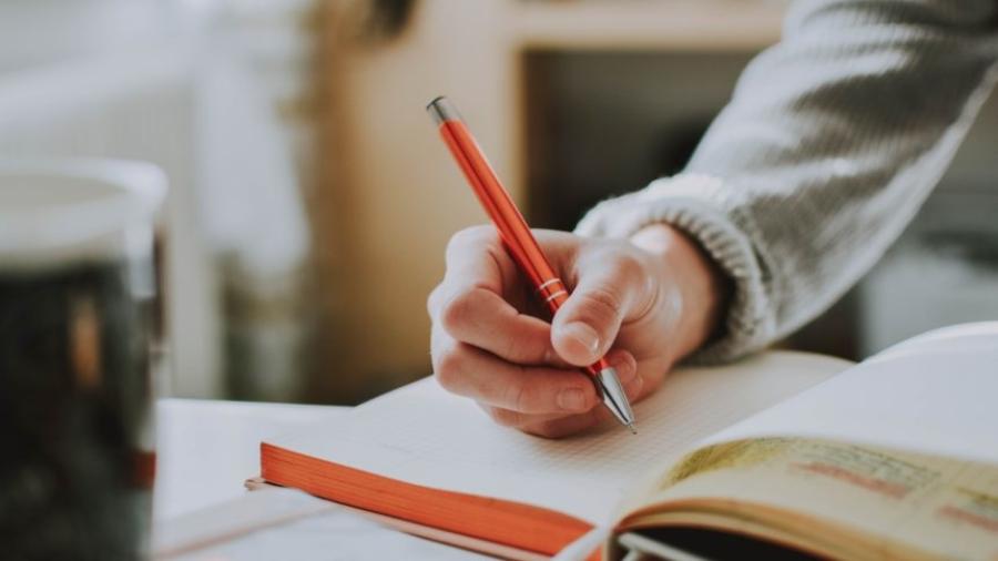person-holding-orange-pen