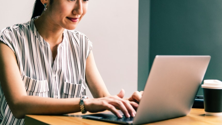 Smiling resume writing career woman typing on her laptop
