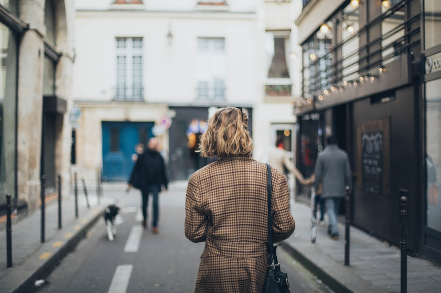 A short haired woman in square patterned coat walking in the streets to look for a successful career change