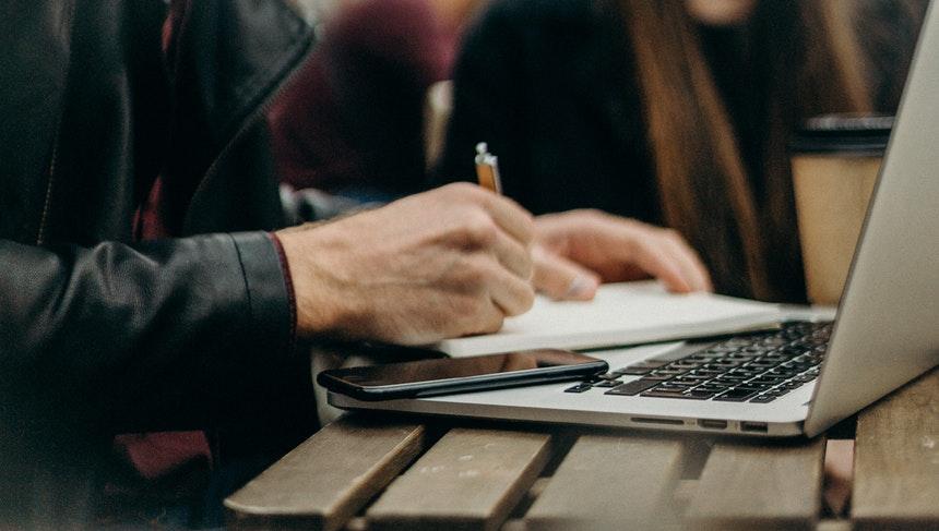 a job seeker writing termination reasons on his resume