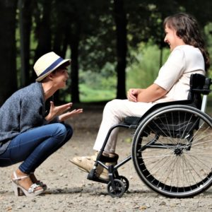 Happy woman sitting in front of a woman in a wheelchair telling about careers for people with disabilities