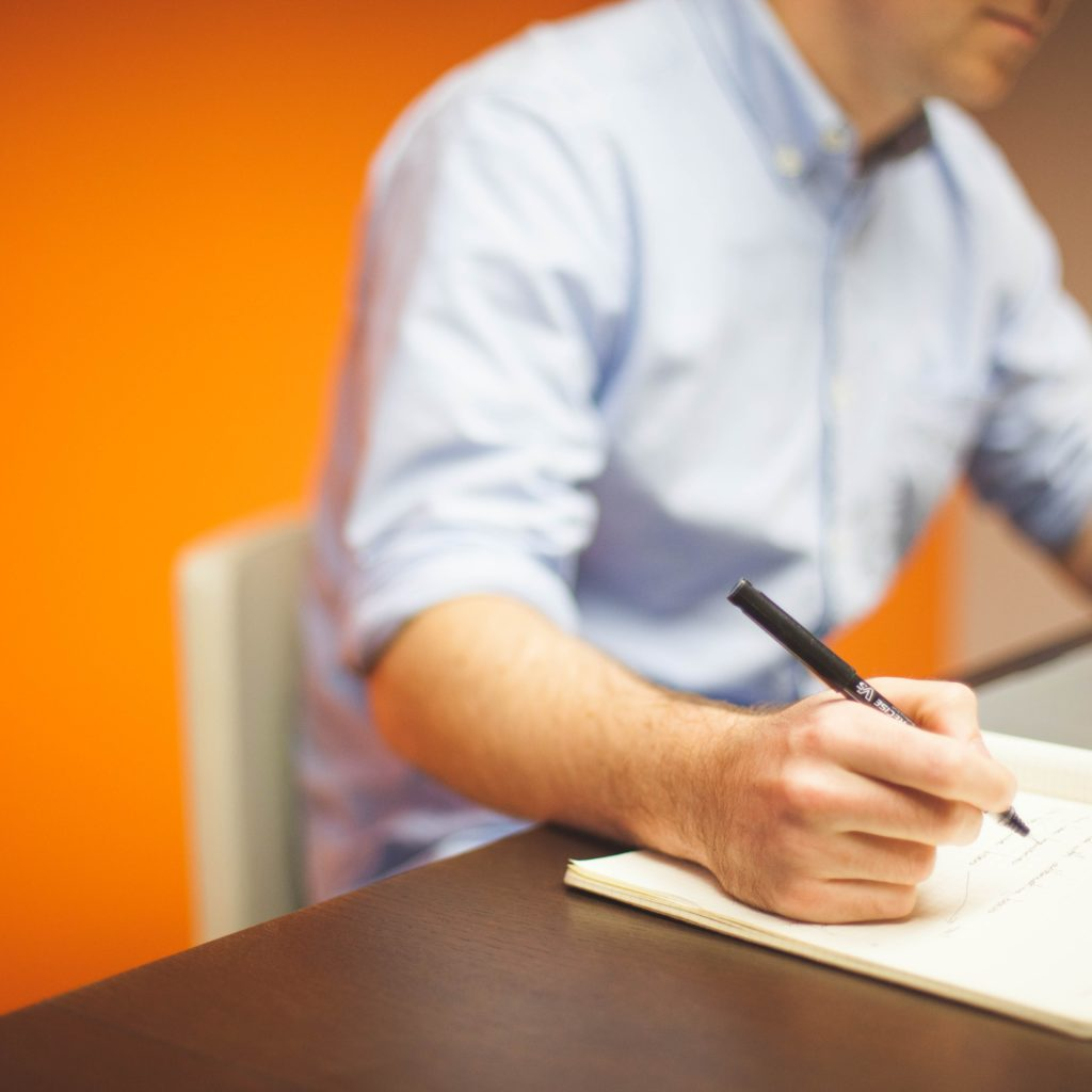 Report Job Discrimination: Man Listing notes on a notebook with yellow background