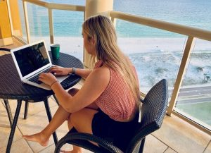 Girl writing a resume while on summer vacation on the beach