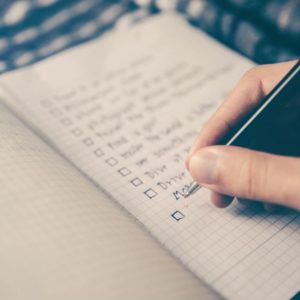 Hand listing job search requirements on a notebook