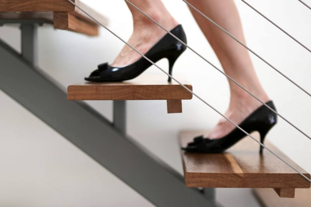 Image of lady climbing ladder for the steps before writing your resume