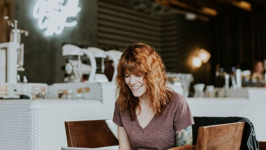 Sending job application signified by red headed woman in front of a laptop