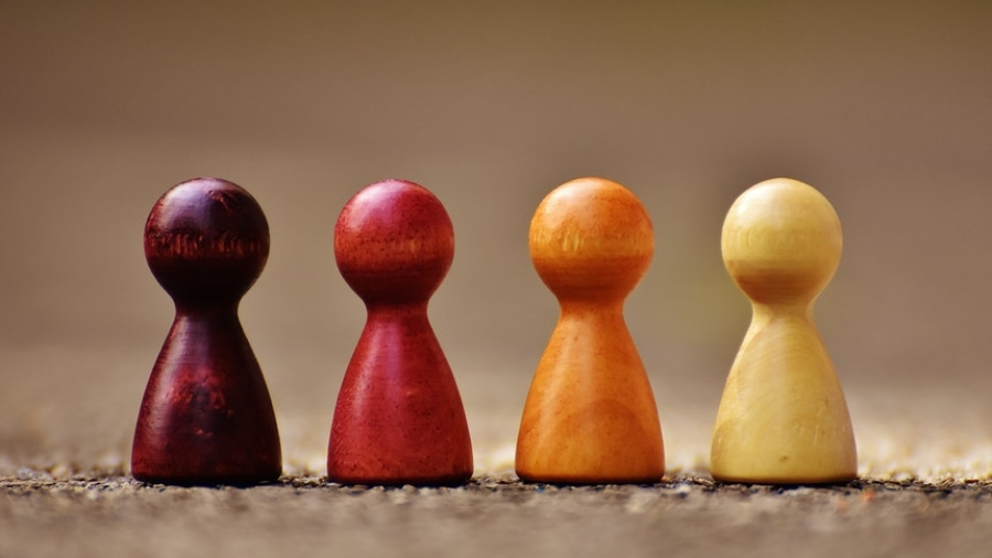 Four chess pieces in different colors to show how diversity training can help build relationship at work