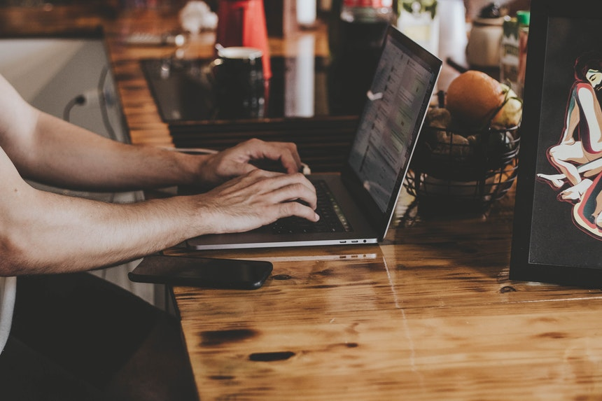 A man is writing an e-resume in his laptop placed on a wooden table