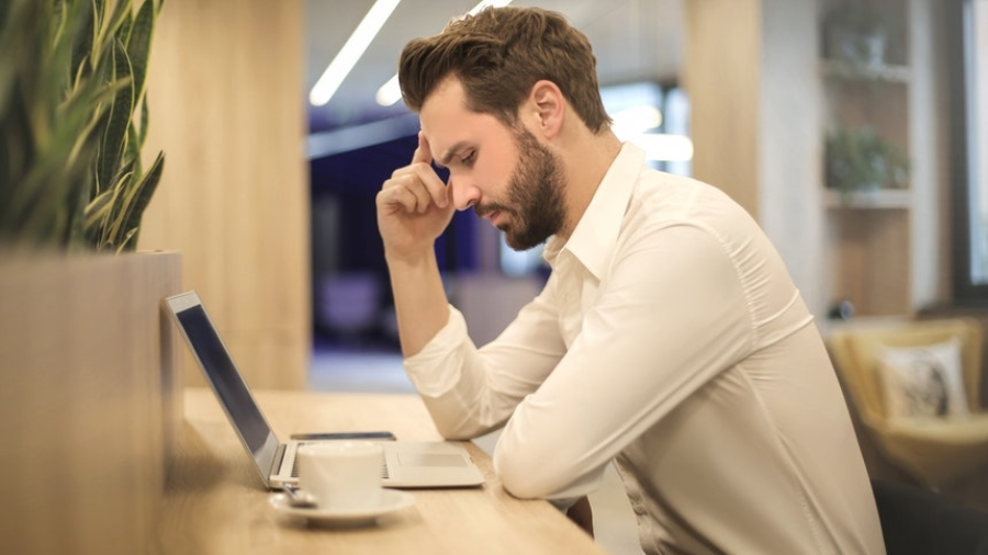 Man deciding if he will hire resume distribution services or not while looking at his laptop