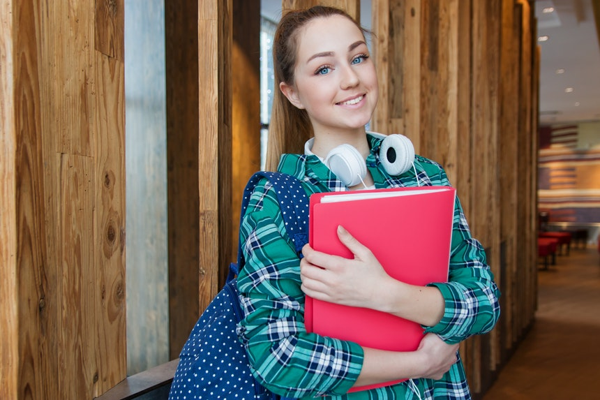 Girl student holding a red folder choosing a college degree