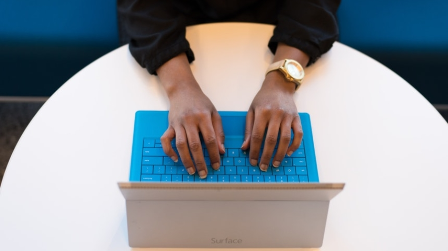 A woman wearing long sleeves is writing objectives for resume in her laptop