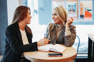 Girl mentoring her friend how to write a marketing specialist resume