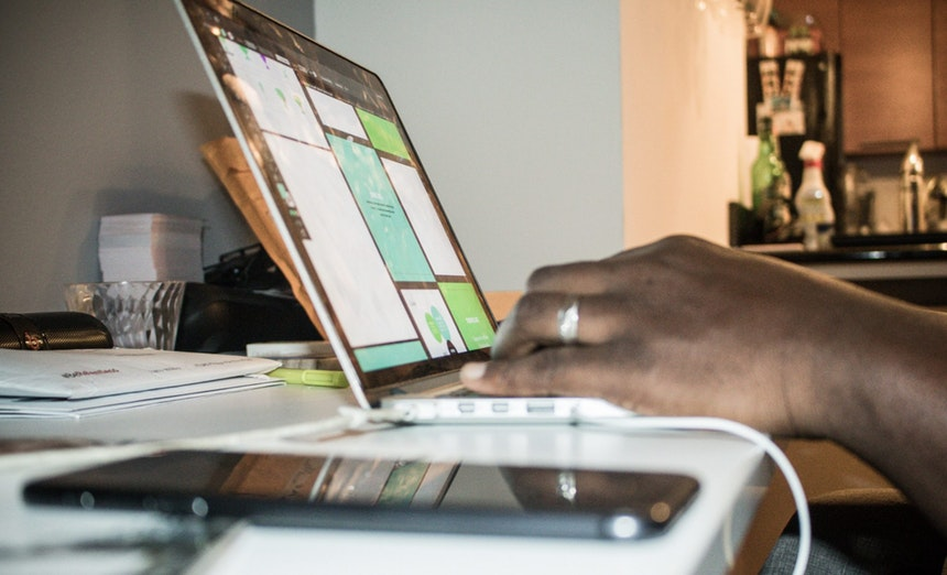 person using a laptop to create an advertising resume
