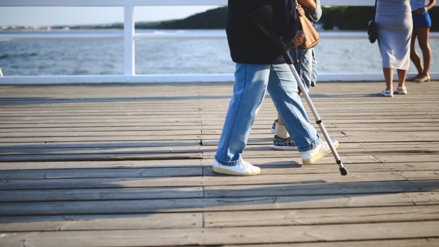 person walking with crutches who needs resume writing tips for people with disabilities