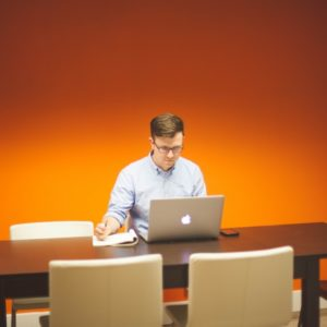 A man wearing a white long sleeves is using his mac laptop in job networking