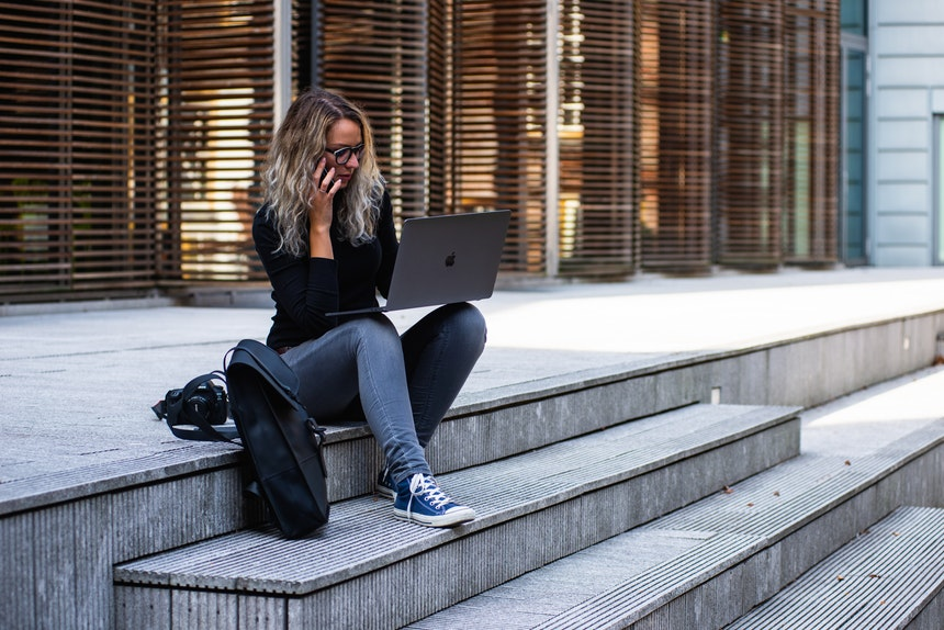 A woman sitting in a pavement while holding her laptop and phone in search for career success