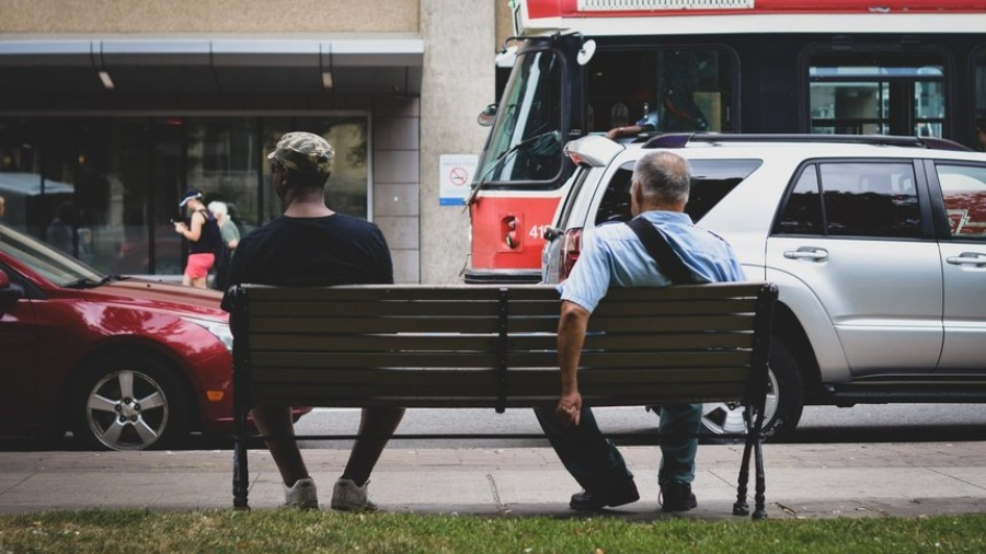 Two men sitting on a bench depicting the current unemployment situation of the US