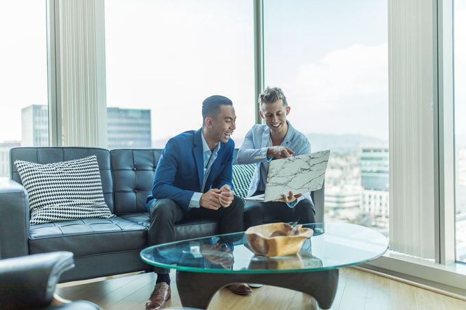 Two men in suits inside an office discussing about best paying temporary jobs