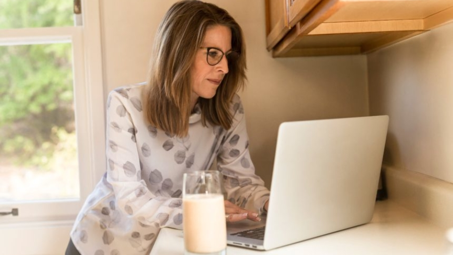 A working mom using her laptop with a glass of milk at her side