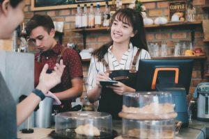 Smiling female hourly worker taking customer orders