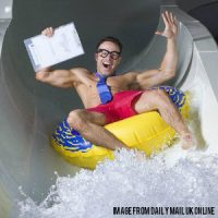 a happy guy sliding through a waterslide