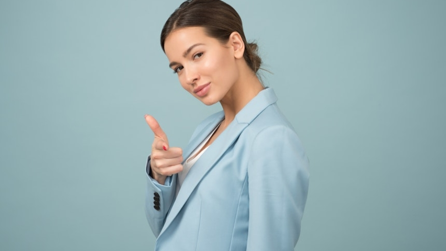 A productive career woman wearing a light colored blazer while pointing a finger gun to you