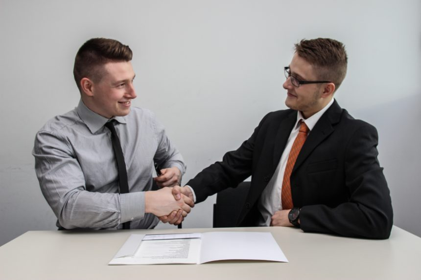 two office mates exchanging funny job interview stories