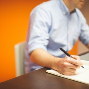 one of the best resume writers working in front of a laptop with a pen and notebook