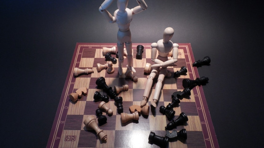 A chess board game with messy pieces and two wooden mannequins showing career dilemmas