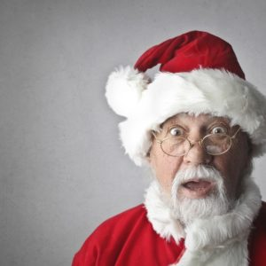 An old beard man dressed like santa claus shocked about holiday job search