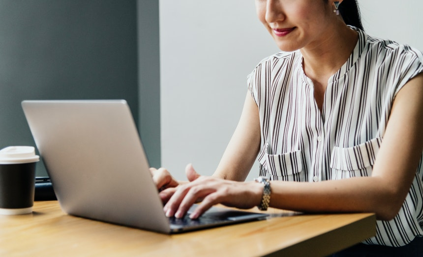 smiling woman searching for best resume format for 2018 while sitting in front of a laptop