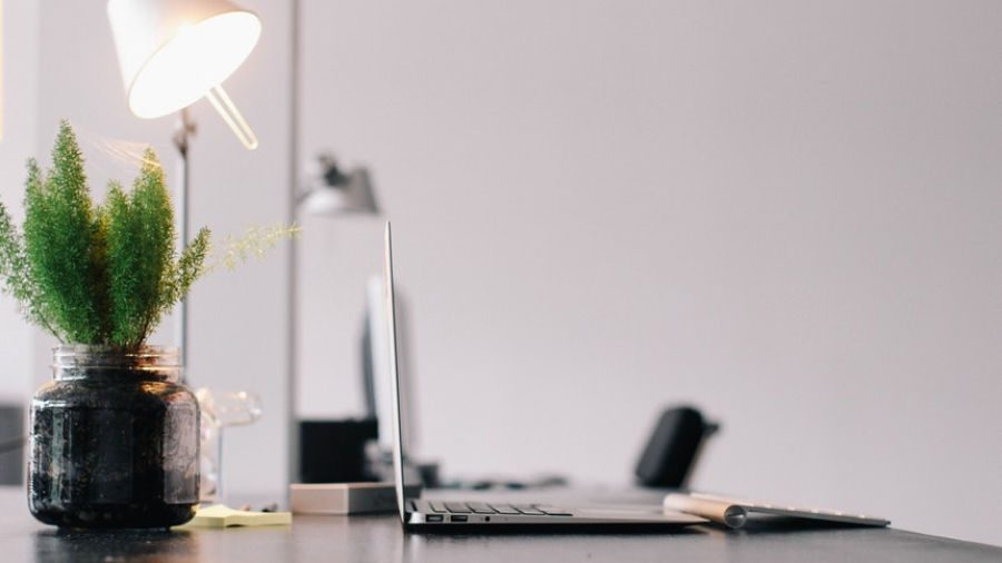 A clean and tidy work space with lamp and laptop to conquer job boredom