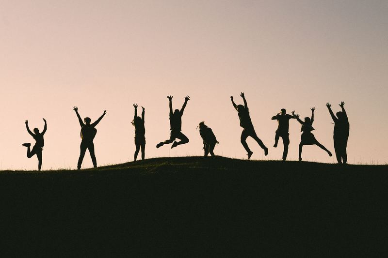 Sillouette of a group of people jumping at the same time to signify teamwork