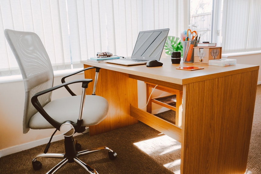 A cozy office with an orange wooden table and gray swivel chair you can use to turn your job into career successfully