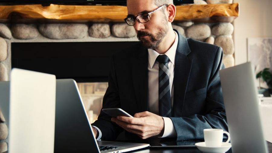 man in suit in front of a laptop searching for executive resumes online while holding a smartphone
