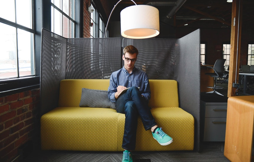 a man sitting pretty in a couch browsing for the best resume writing services to hire