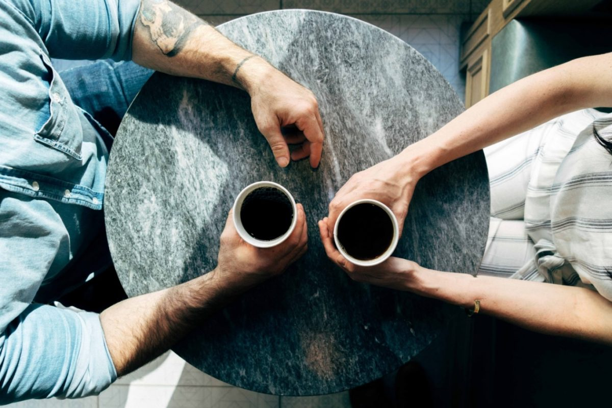 A man and a woman holding coffee and facing each other discussing several job interview stories with each other.