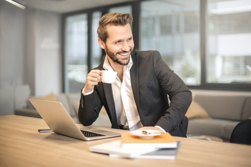 Man in front of a laptop looking for the best executive resume writing services