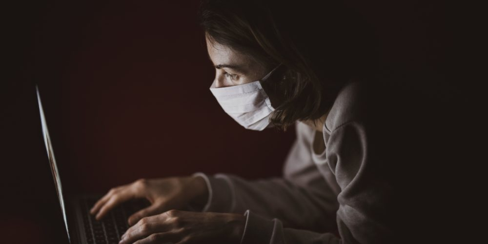 Woman with face mask using laptop